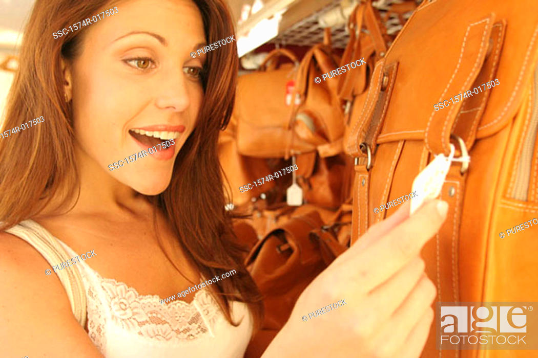 Stock Photo: Close-up of a young woman looking at the price tag on a bag in a store.