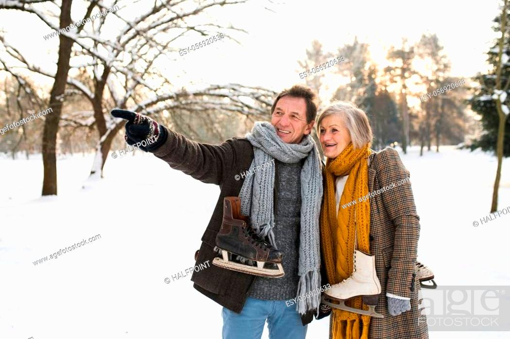 Imagen: Beautiful senior woman and man in winter nature with ice skates going to outdoor rink.