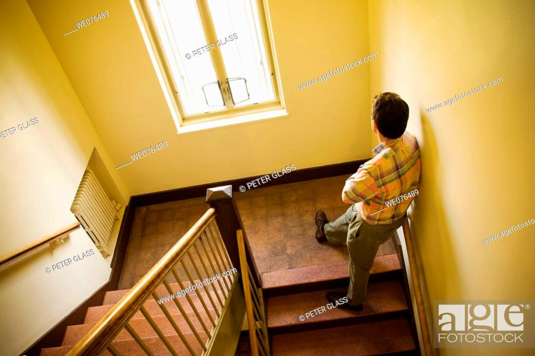 Stock Photo: Man on a stair in an office building stairwell.