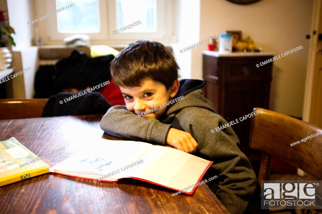 Stock Photo: child sitting at the table in the kitchen at home with book.