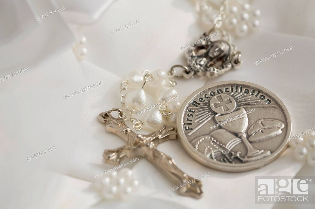 Imagen: First communion book, rosary beads with silver cross, white religious dress.