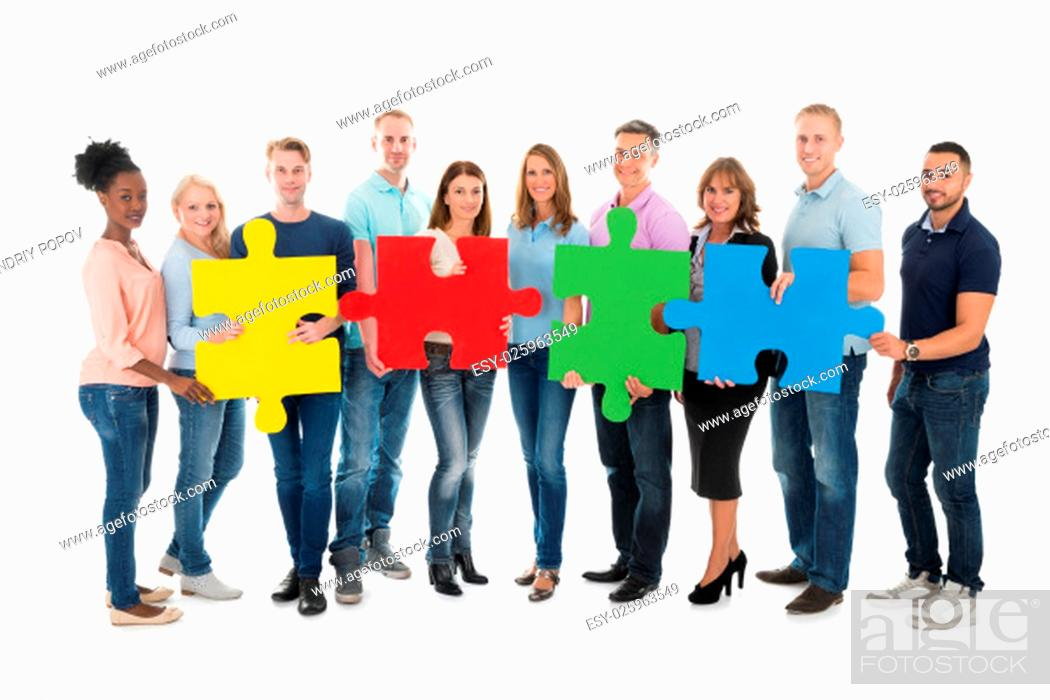 Stock Photo: Full length portrait of creative business people holding jigsaw pieces against white background.