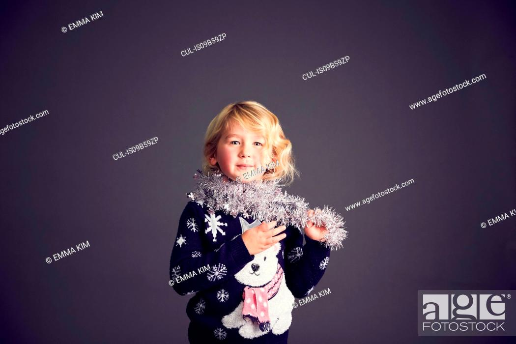 Stock Photo: Portrait of young girl wearing Christmas jumper and tinsel around neck.