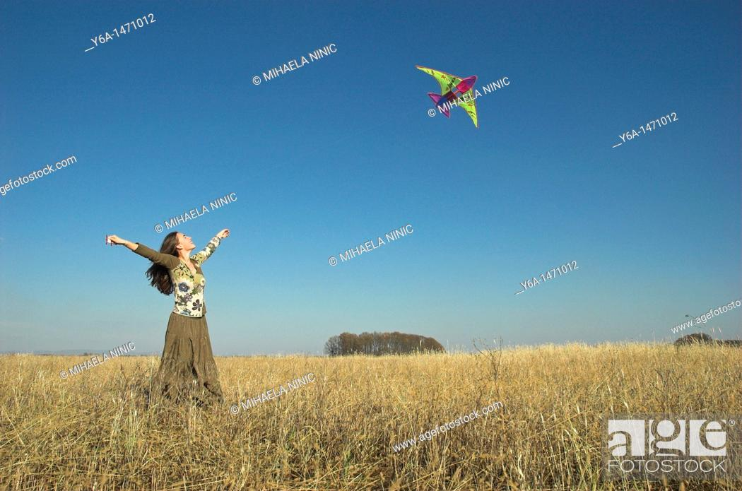 Stock Photo: Young woman in field flying kite.
