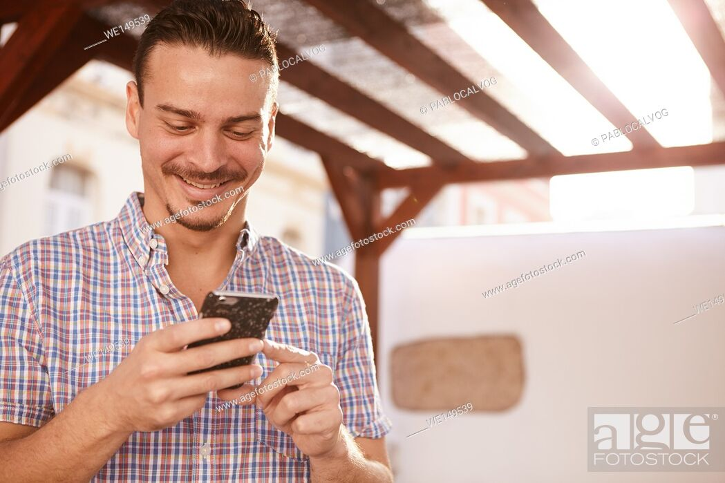 Stock Photo: Cute dark haired guy grinning from ear to ear with satisfaction while looking at his cellphone that he is holding with both hands.