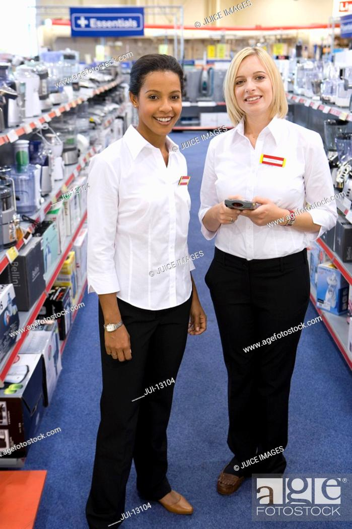 Stock Photo: Young saleswoman with colleague in shop, smiling, portrait.