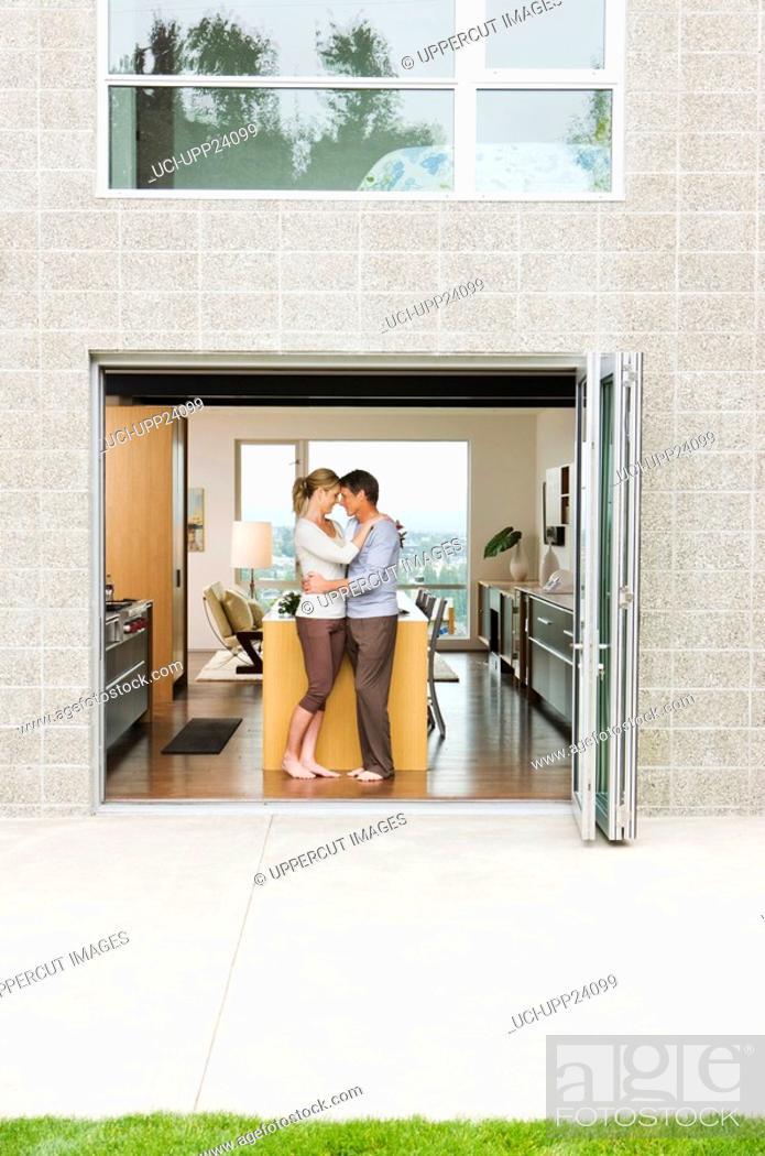 Stock Photo: Hugging couple standing in open patio doorway.