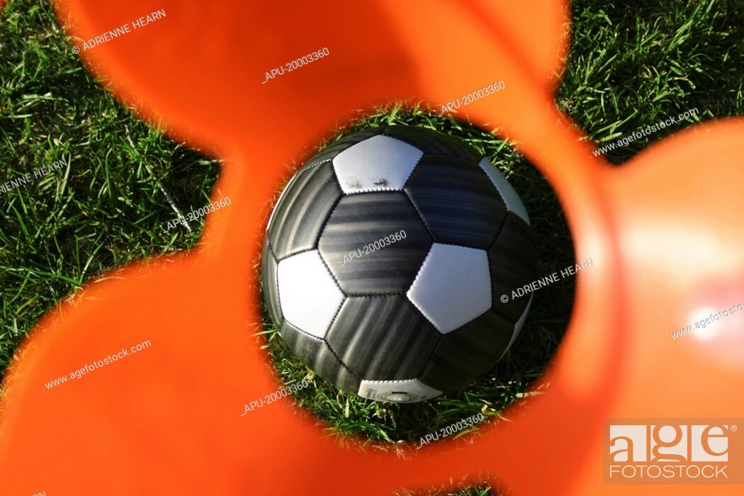 Stock Photo: Football viewed through eye of a practise cone.