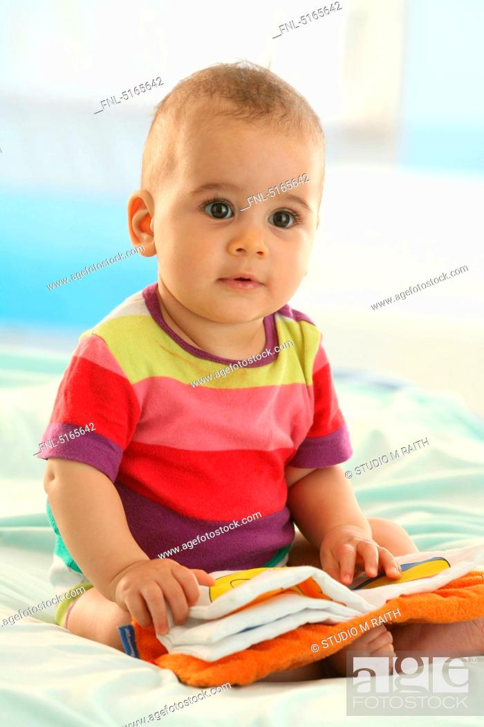 Stock Photo: Baby sitting on bed.