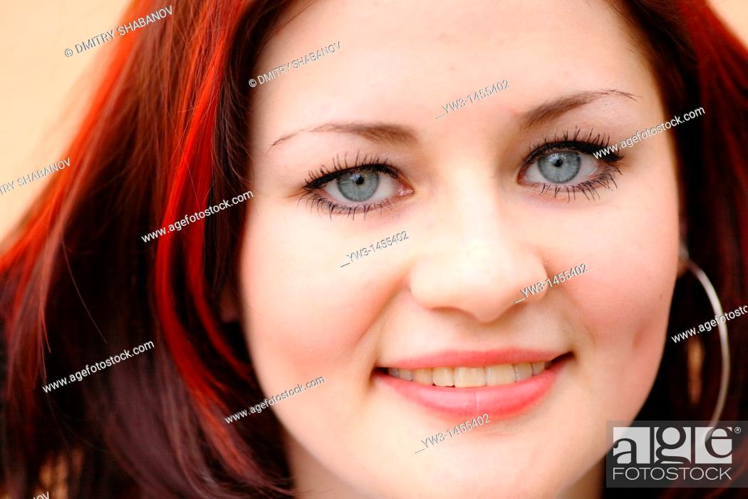 Stock Photo: redhead women outdoors agains painted wall.