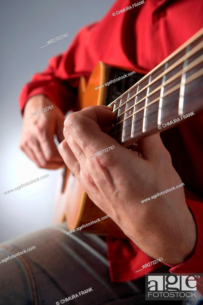 Imagen: closeup of hands of a musician playing acoustic guitar.