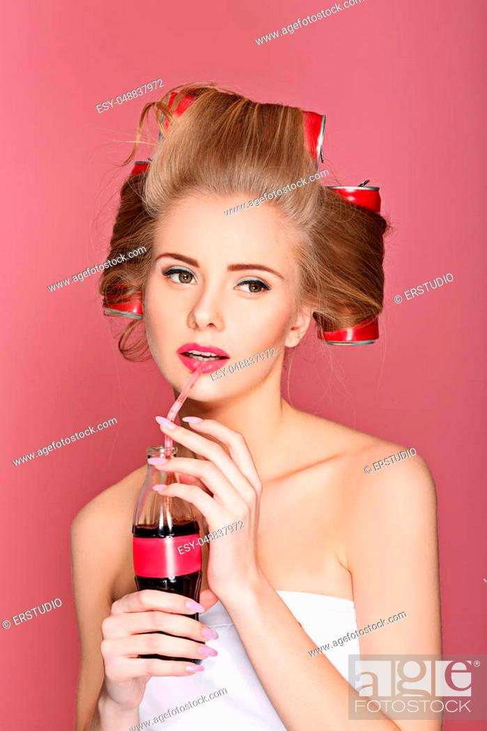 Stock Photo: Beautiful fun curly blond woman holding glass bottle with soda over pink background.