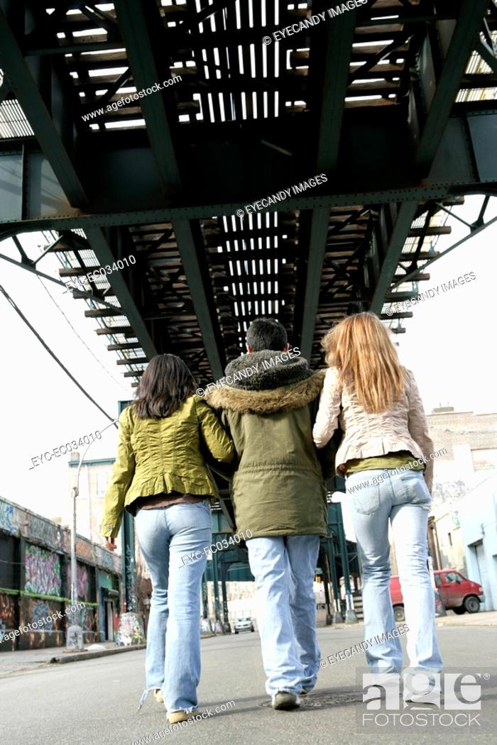 Stock Photo: Rear view of three people walking.