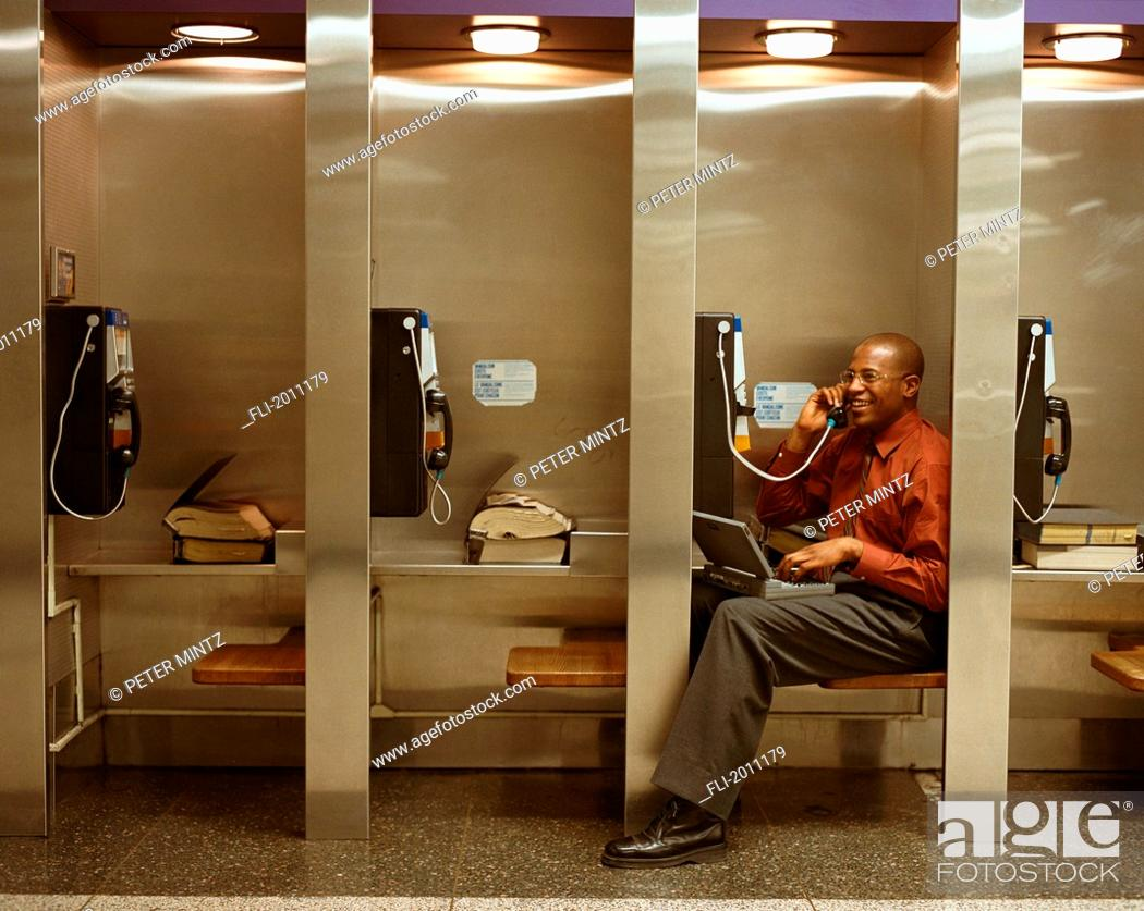 Imagen: Fv3208, Peter Mintz; Businessman Talking On Payphone In Row Of Phones, Using Laptop.