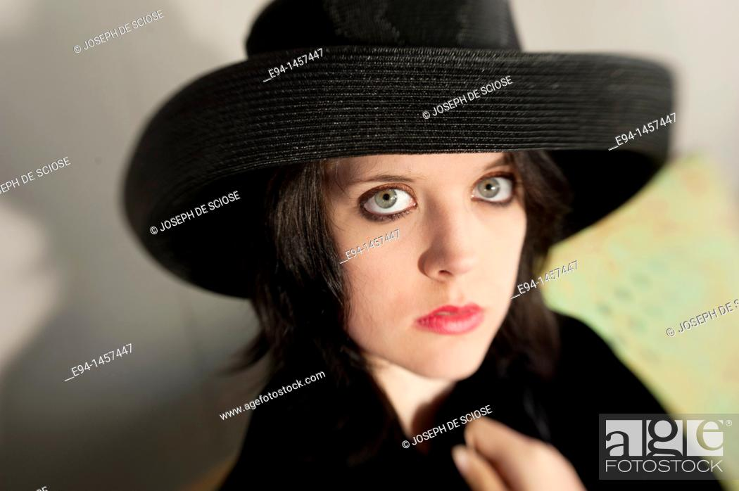 Stock Photo: Portrait of a nineteen year old brunette woman looking at the camera wearing a black hat.