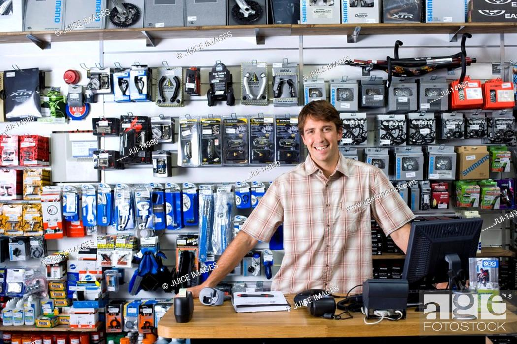 Stock Photo: Shop assistant behind counter, smiling, portrait.