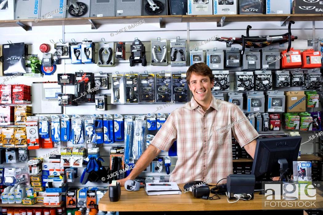 Stock Photo: Shop assistant behind counter, smiling, portrait.