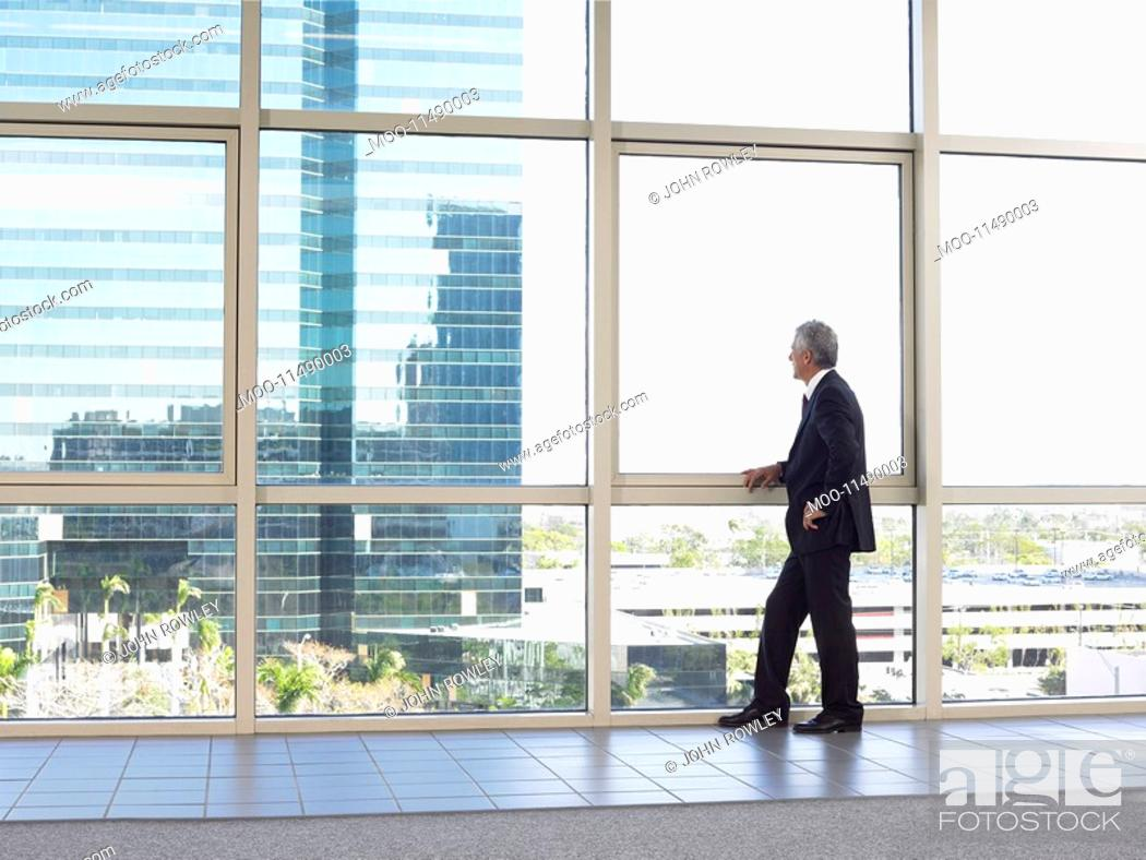 Stock Photo: Businessman looking out of office window.