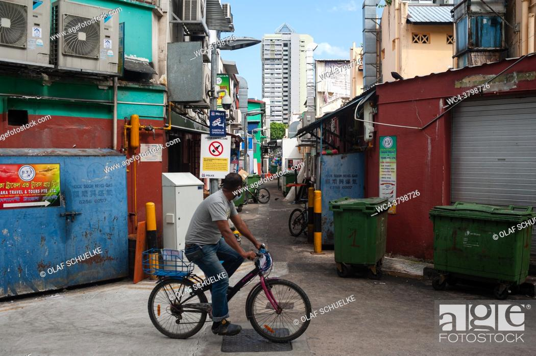 Imagen: Singapore, Republic of Singapore, Asia - A man wearing a face mask cycles through a narrow side street in Little India city district during the lasting corona.