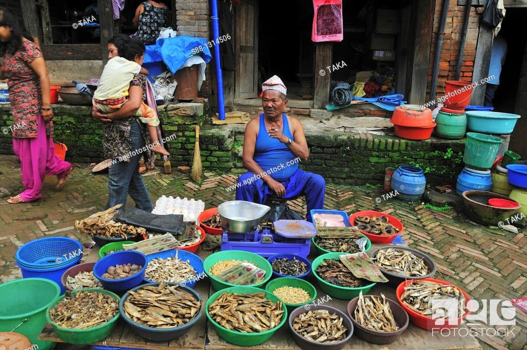 Stock Photo: In the morning market the man selling dry fishes. Bhaktapur, Kathmandu Valley, Nepal.