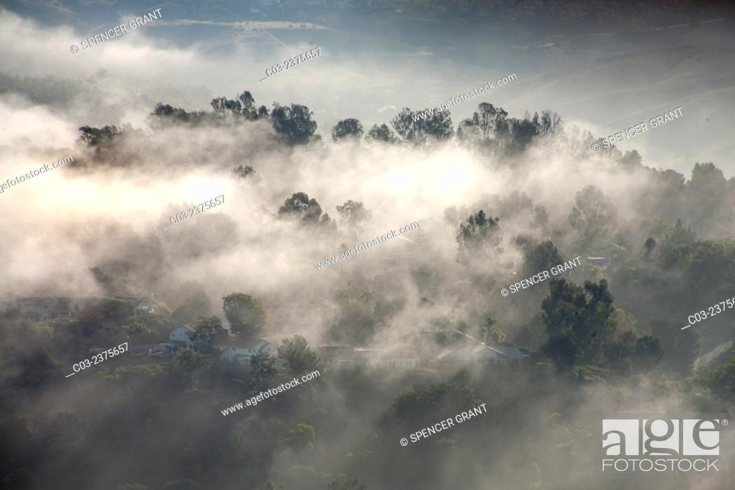 Stock Photo: Early morning sun dissipates sea mist around residential homes in Crown Valley in coastal Laguna Niguel, CA.