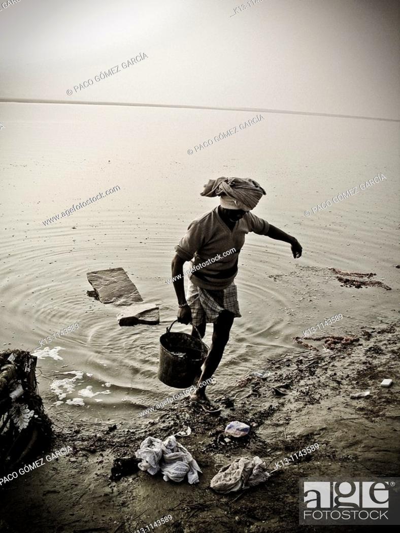 Stock Photo: Man taking water from the Ganges river  Varanasi banaras  Uttar Pradesh  India.
