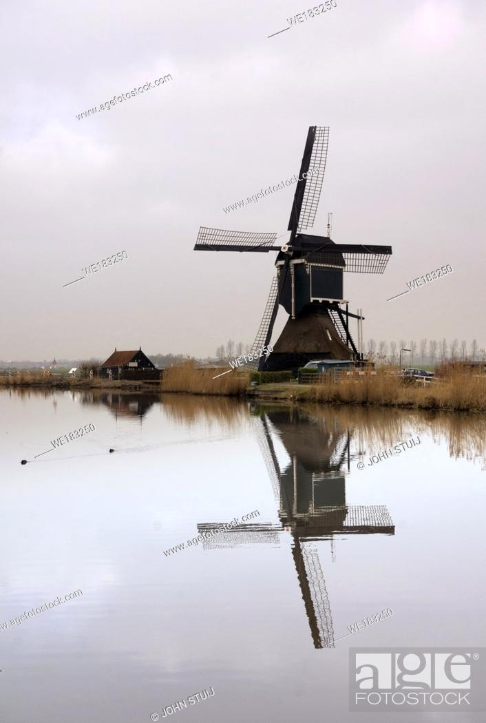 Stock Photo: The Achterlandse windmill along the canal called Ammersche Boezem near Groot-Ammers in the Dutch region Alblasserwaard.