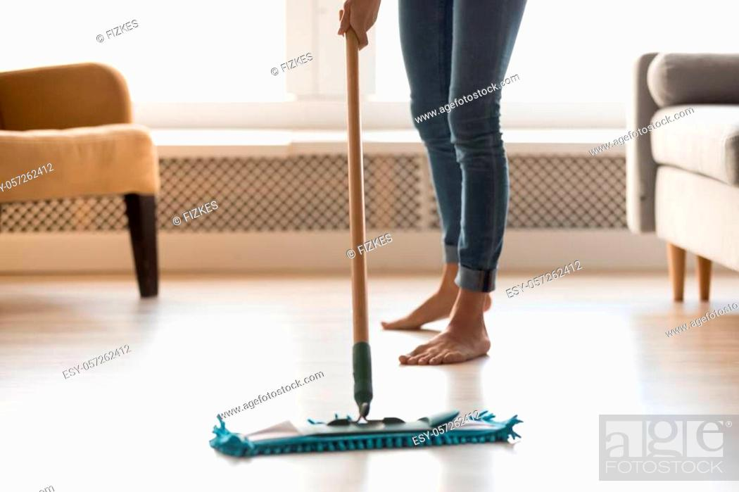 Photo de stock: Close up cropped image of barefoot woman in casual clothes make house chores cleaning warm heated wooden laminate floor using wet mop.