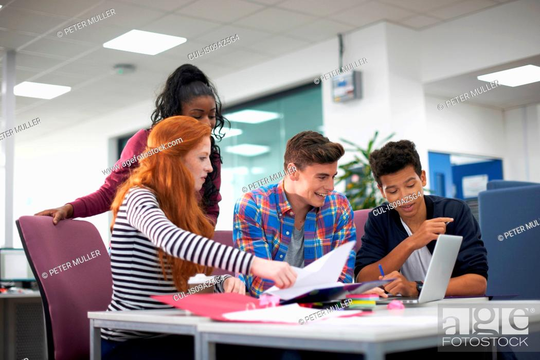 Photo de stock: Four young adult college students teamworking at desk.