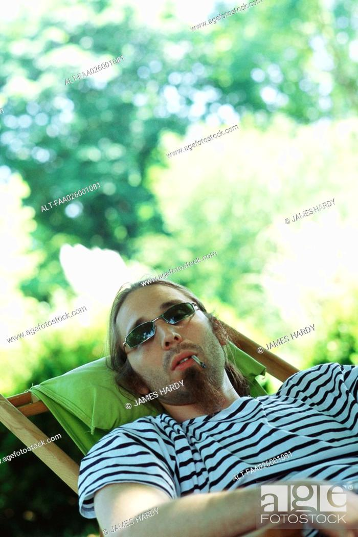 Stock Photo: Man wearing sunglasses reclining in chair, smoking hand-rolled cigarette.