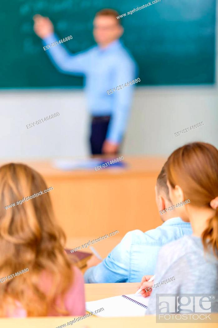 Stock Photo: Brief revisal. Young male college professor is busy with explaining and revising the lecture he has given.