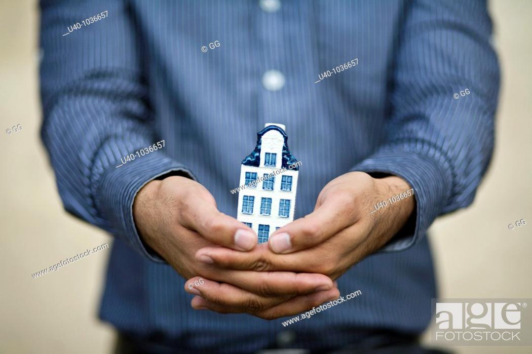 Stock Photo: hands holding new home.