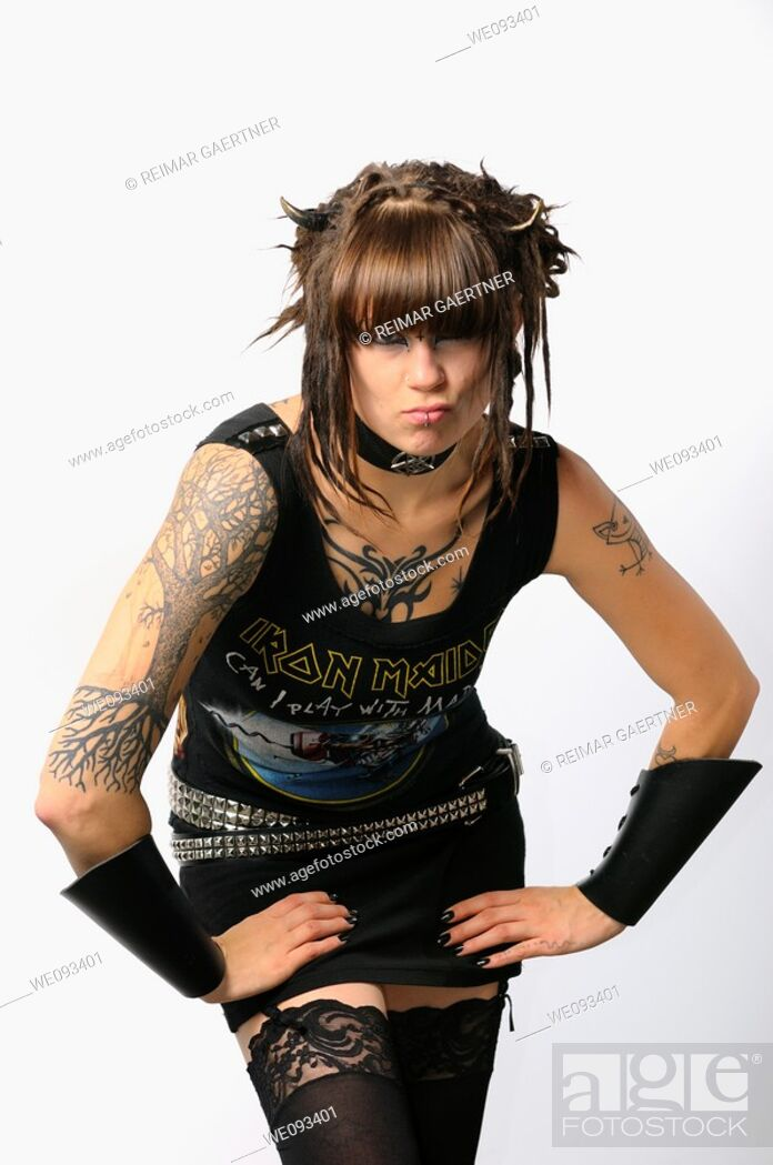 Stock Photo: Young pouting heavy metal lady with horns piercings and tattoos on a white background.
