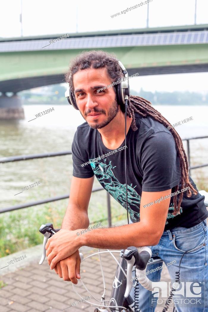 Stock Photo: Man with long rasta hair on bike at river Rhine in Bonn.