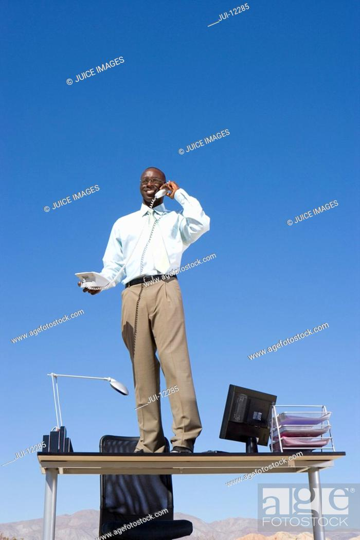 Stock Photo: Businessman standing on desk in desert, using telephone, low angle view.