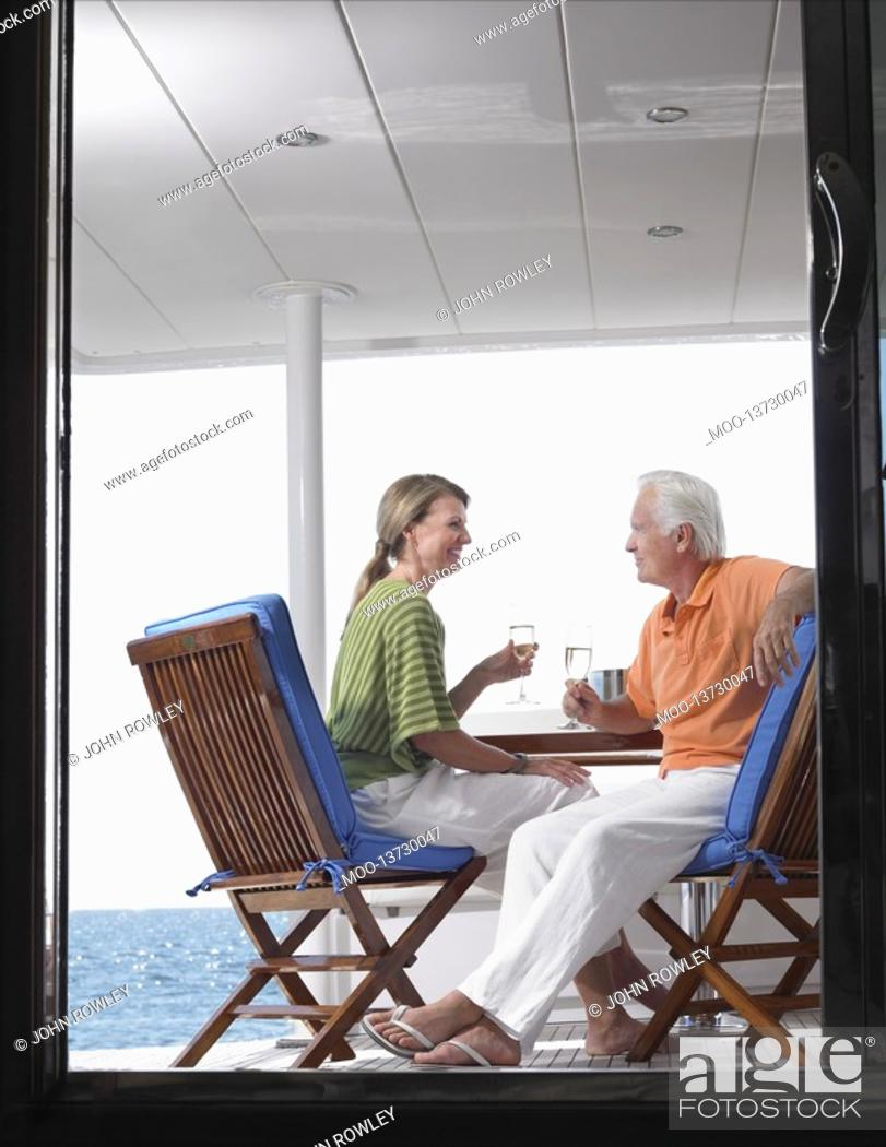 Stock Photo: Middle-aged couple drinking wine on yacht profile view through door.