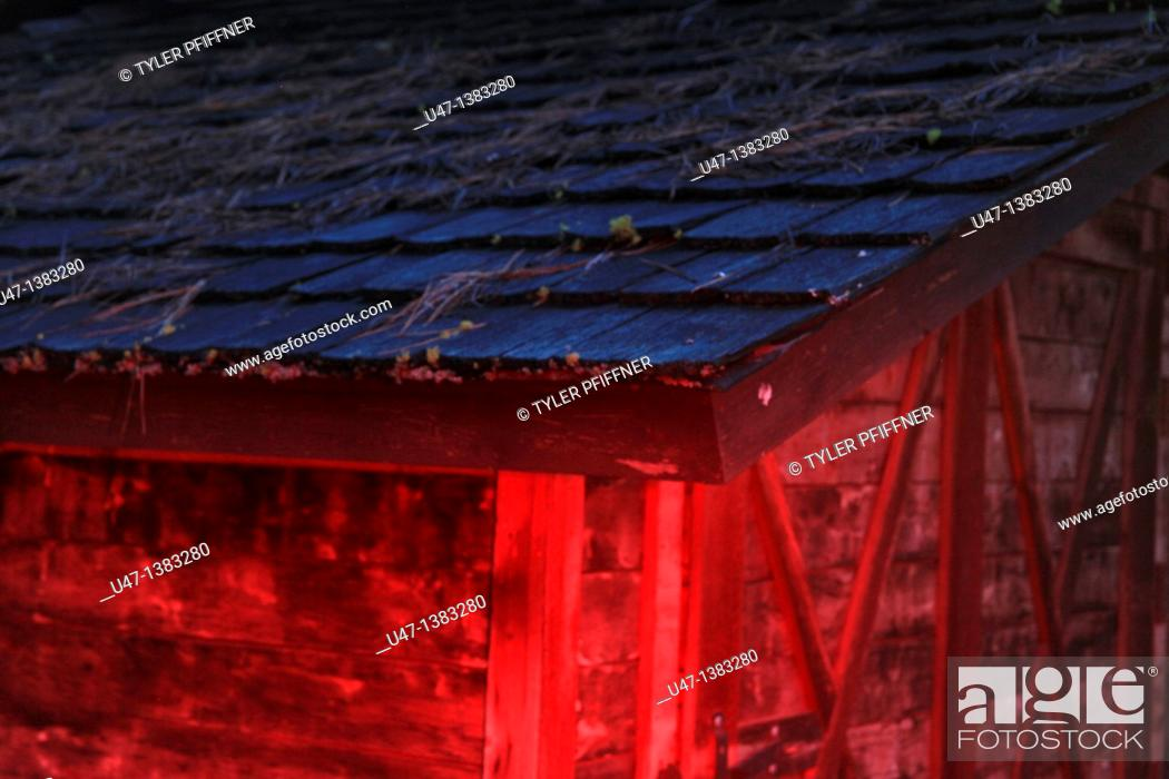 Stock Photo: a picture of a barn roof in the evening light with red light added.