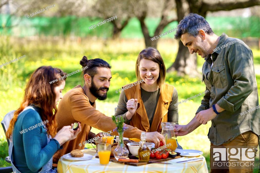 Stock Photo: Friends enjoying a healthy vegan breakfast in the countryside.