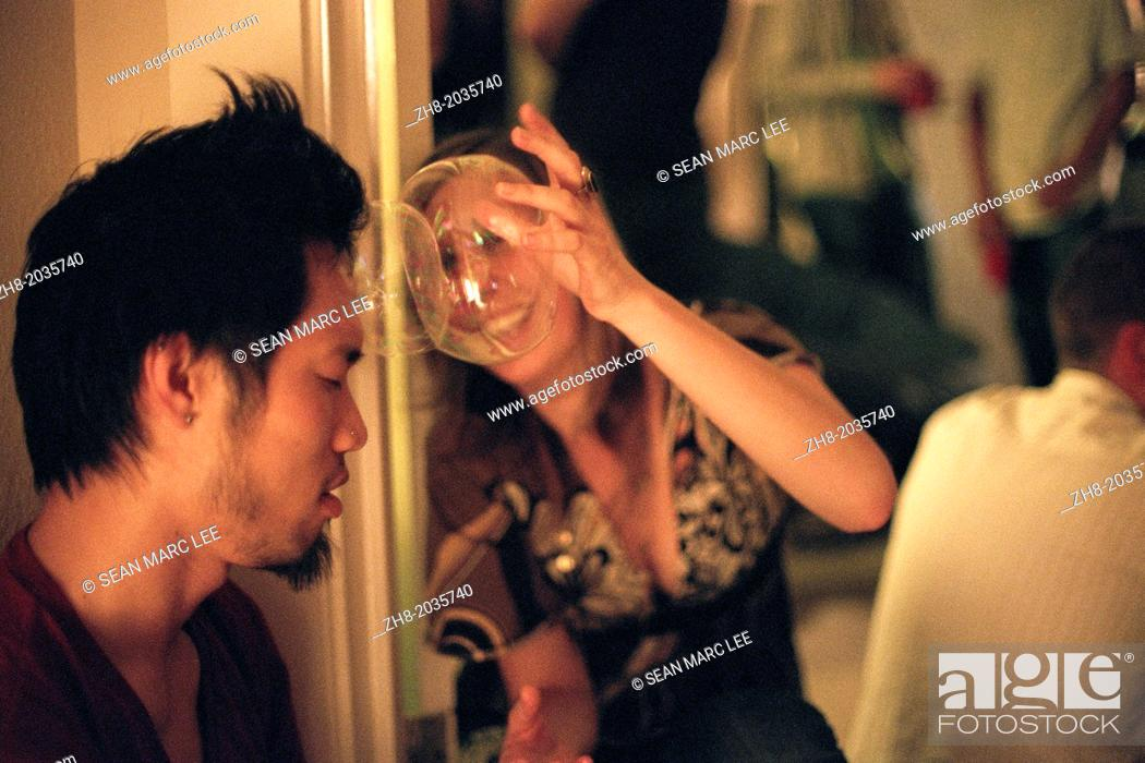 Stock Photo: A woman smashes plastic bubbles on a man's head at a house party in Los Angeles.