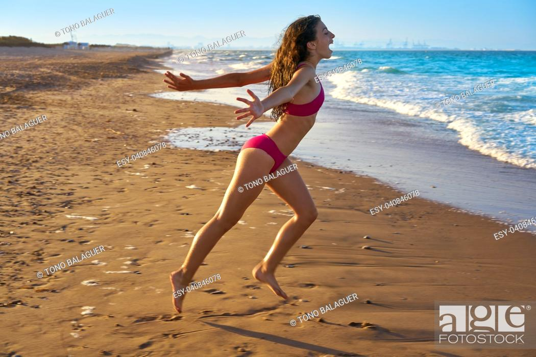 Stock Photo: Bikini girl running to the beach shore water of Mediterranean sea.