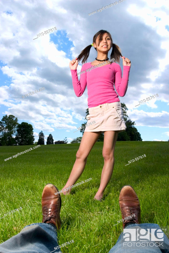 Stock Photo: Young Spanish/Asian woman, in pigtails, and a man's legs and feet, posing at a park.