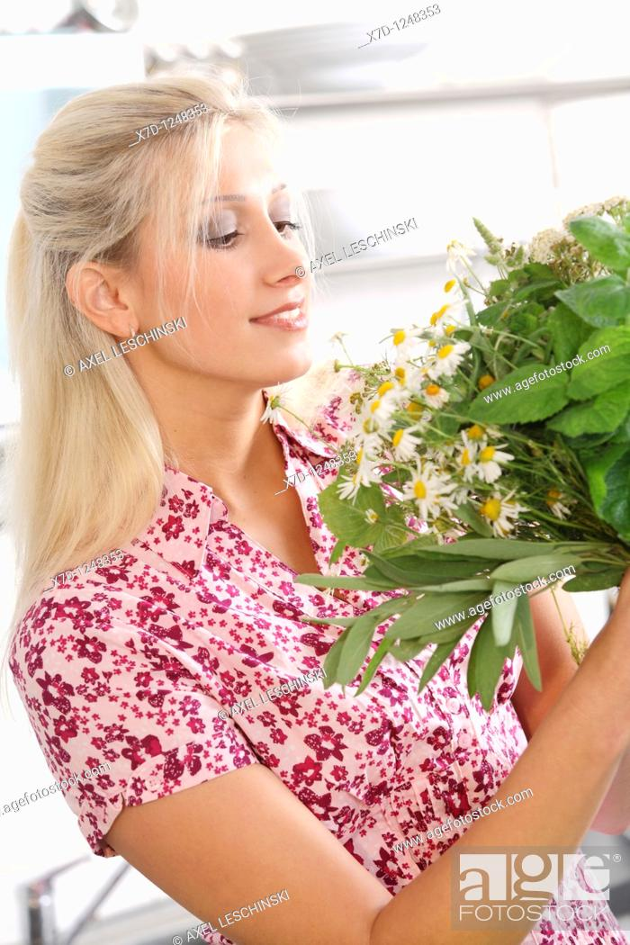 Stock Photo: blond woman holding a bunch of wild herbs.