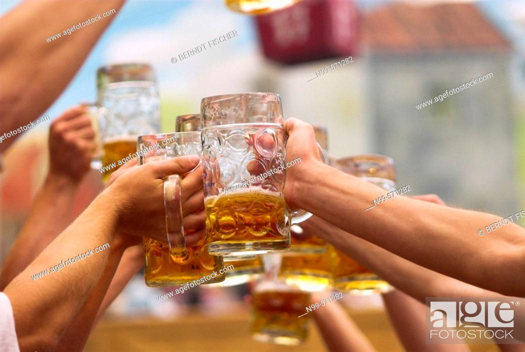 Stock Photo: Young men with beer mugs at Oktoberfest beer tent. Munich, Bavaria, Germany.