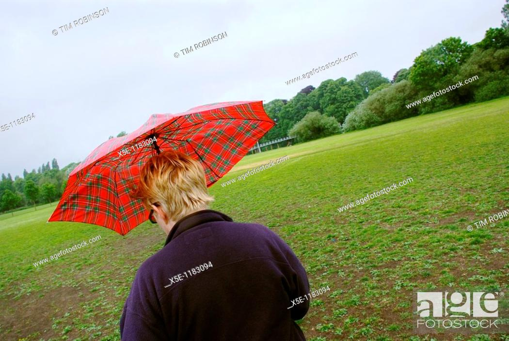 Stock Photo: Rearview adult woman walking in park with umbrella up.