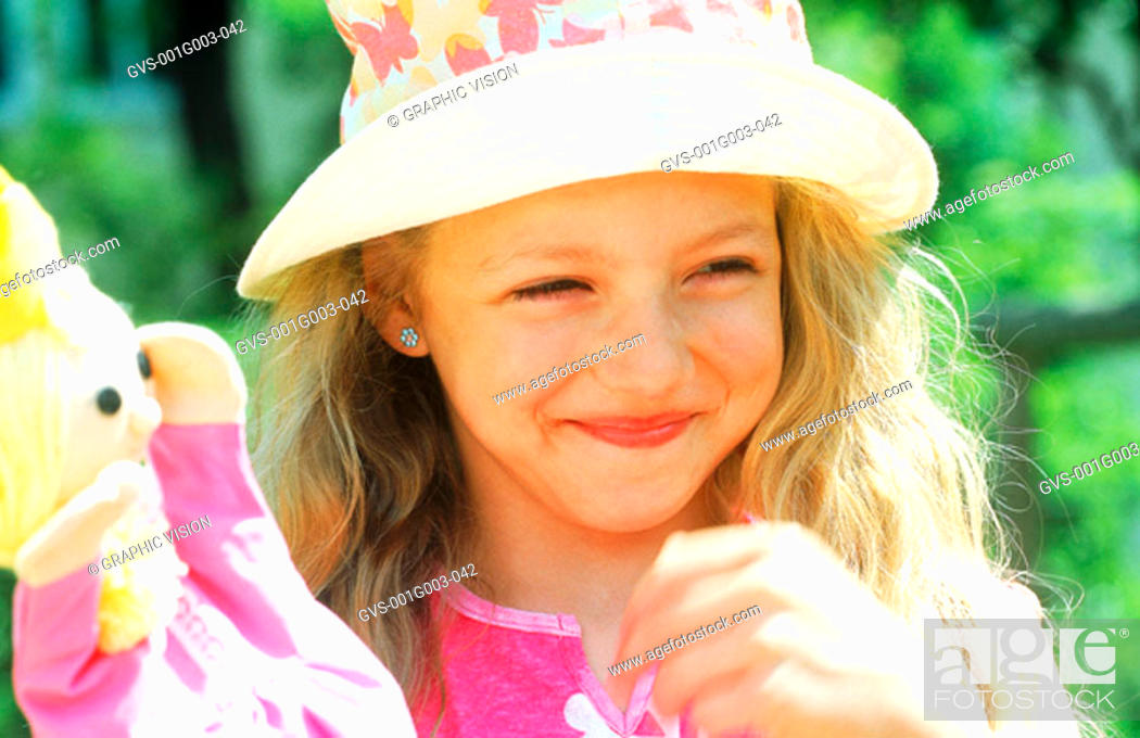 Stock Photo: Young girl smiling and holding a doll.