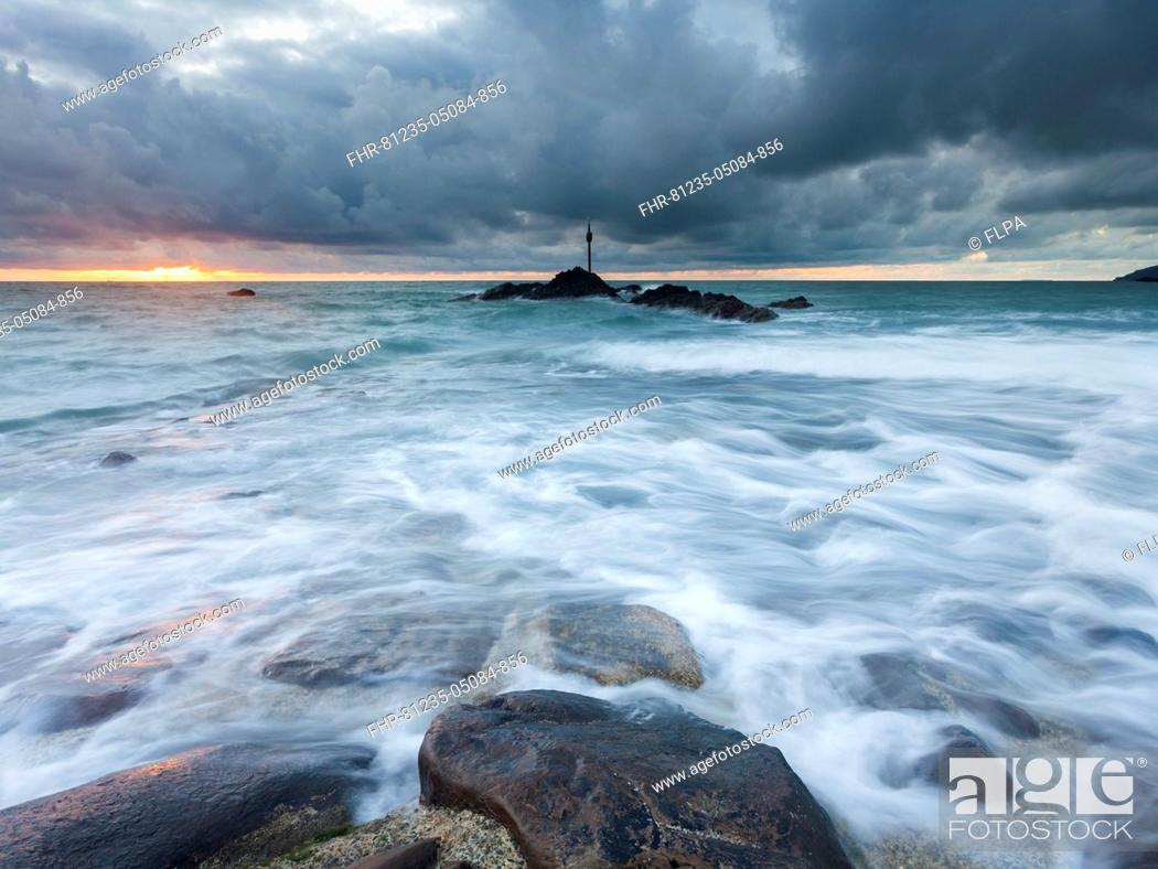 Stock Photo: Waves washing over breakwater under stormclouds at sunset, during one of the highest tides of the year, Bude, North Cornwall, England, 18th August 2015.