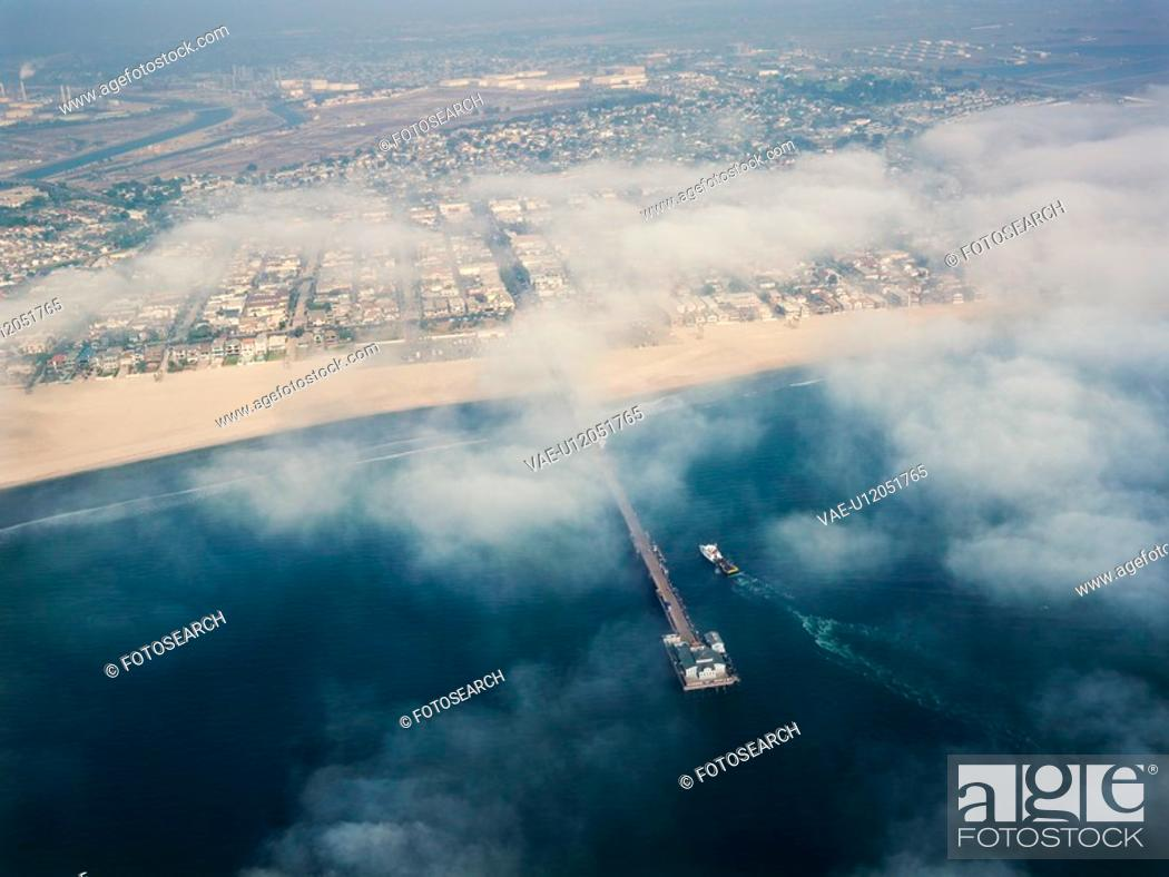 Stock Photo: Aerial view of clouds covering beachfront and fishing pier in southern California.