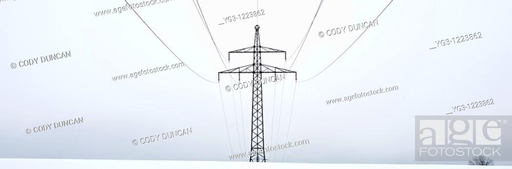 Stock Photo: Electircal power lines on cloudy winter day cross snow covered field, Oberpfalz, Bavaria, Germany.