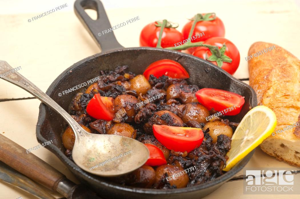 Stock Photo: Baby cuttle fish roasted on iron skillet with tomatoes and onions over rustic wood table.