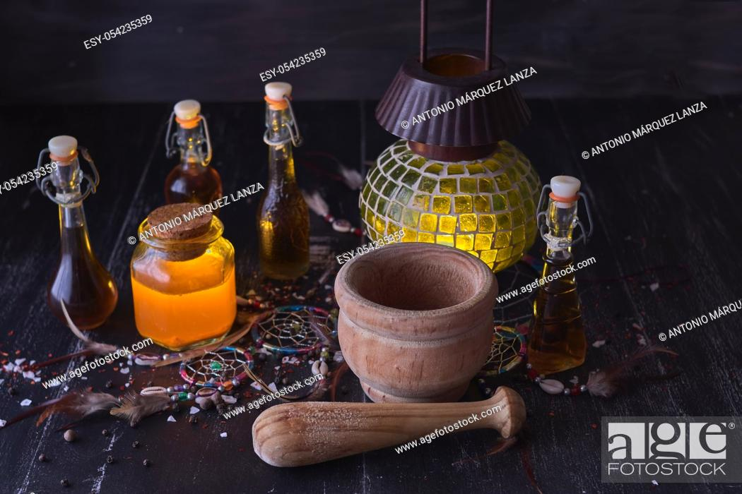 Stock Photo: Magic luminous alchemy potions, old lantern on dark background over black wood with an Indian amulet.